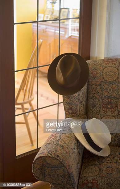 Two hats on chair indoors