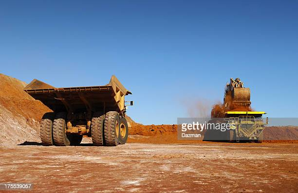 Two haul trucks being loaded with ore.