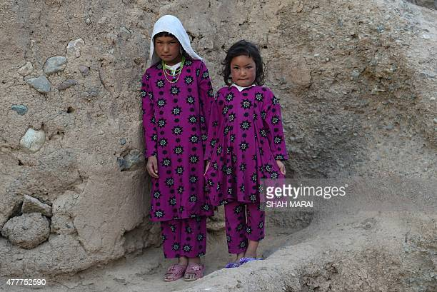 Two Hazara Afghan girls pose for a photograph in Bamiyan on July 19 2015 Bamiyan some 200 kilometres northwest of Kabul stands in a deep green and...