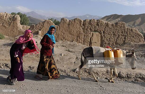 Two Hazara Afghan women walk with their donkey loaded with cans of water in the old city of Bamiyan on July 31 2010 Bamiyan some 200 kilometres...