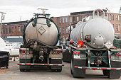 Two hazardous waste tanker trucks for picking up petroleum from ships in harbor