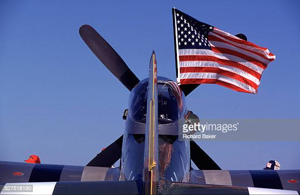 Two heads wearing aviation caps seen just over the striped wings of a WW2era P51 Mustang fighter plane during the world's largest aviation airshow at...