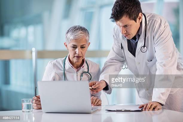 Zwei Arbeitnehmerinnen im Gesundheitswesen arbeiten gemeinsam auf einem laptop.