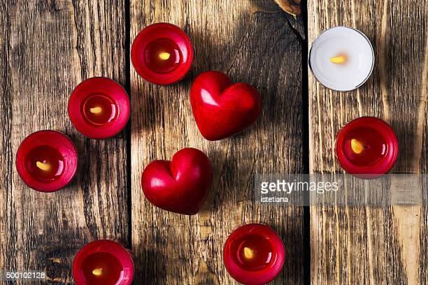 Two hearts and red candles on rustic wooden board, Valentines day background, top view