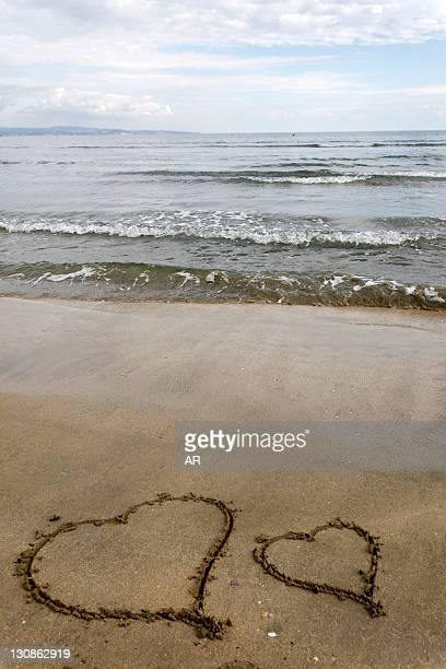 Two hearts carved into the sand on a beach
