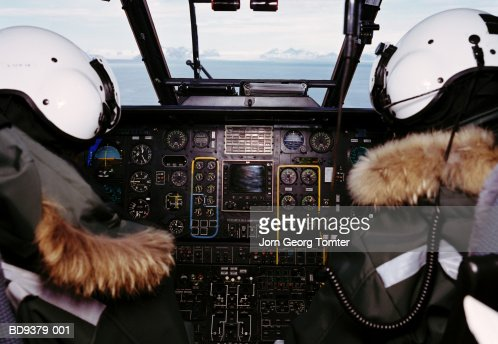 Two helicopter pilots in cockpit, rear view : Stock Photo