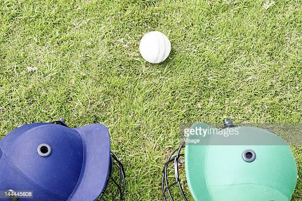 Two helmets and a white cricket ball