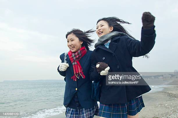Two high school girls running on the beach