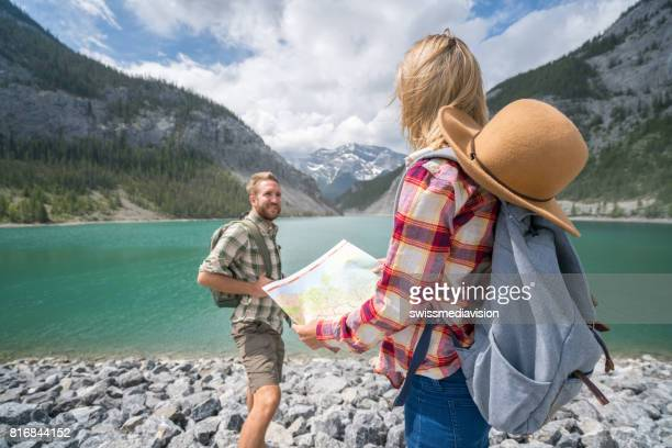 Two hikers by mountain lake consulting trail map
