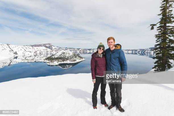Zwei Wanderer in den verschneiten Bergen mit Blick auf einen See