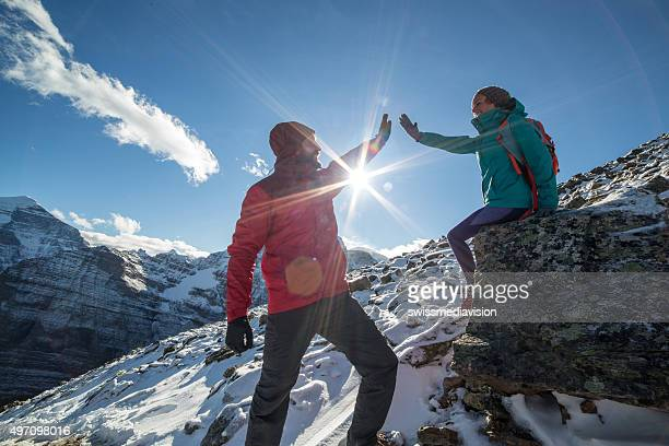 Two hikers on snowcapped rocky mountains celebrating