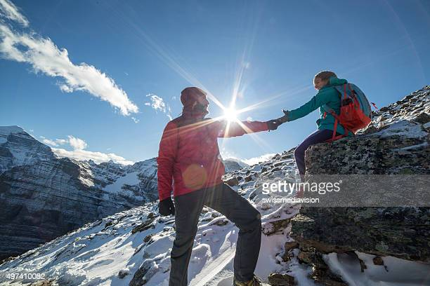 Two hikers on snowcapped rocky mountains