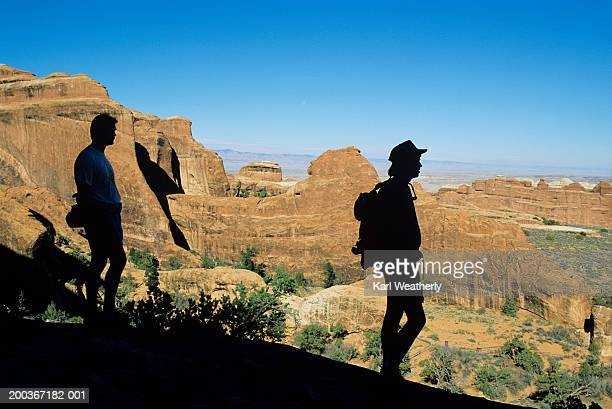 Two hikers seen as silhouettes in Arches National Park, Utah, USA