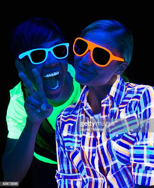 Two hip people under black light