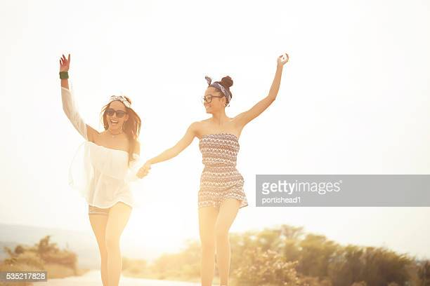 Two hippie women holding hands and dancing on the road