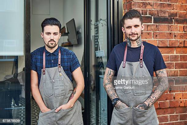 Two Hipster Barbers stood outside their shop