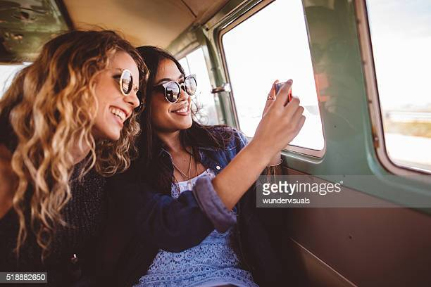 Two Hipster Girls Sitting Together taking a road trip photo