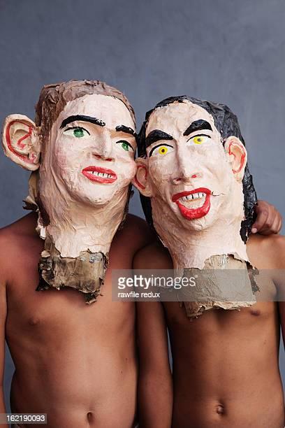 Two hispanic kids wearing paper masks.