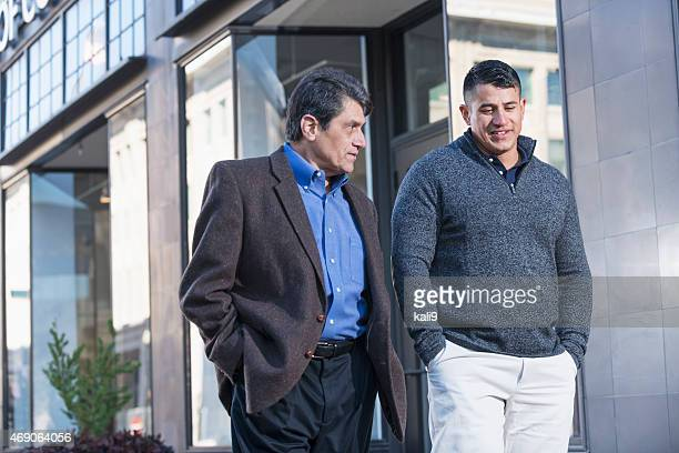 Two Hispanic men talking, walking down city sidewalk