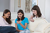 Two Hispanic teenage girls listening to an MP3 player with their friend