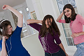 Two Hispanic teenage girls listening to MP3 players and dancing with their friend