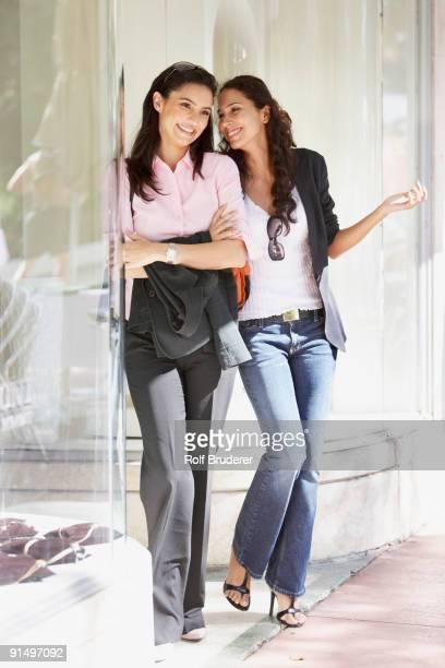 Two Hispanic woman next to store window