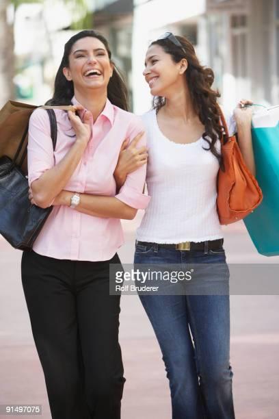 Two Hispanic women with shopping bags