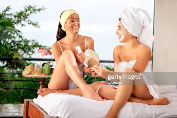 Two Hispanic young woman sharing beauty treatments at home or spa.