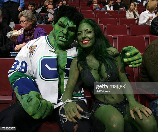 Two hockey fans dressed up in costumes sit in the stands before a game between the Vancouver Canucks and the Nashville Predators game on Halloween at...