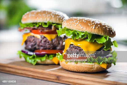 Two Home Made Huge Cheeseburger on oak chopping board