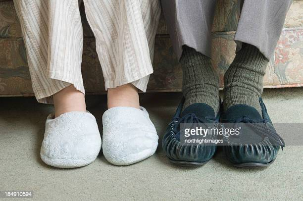 Two home slippers worn by people sitting on the couch