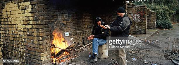 Two homeless men warm themselves on a fire made in a shopping trolley in Hackney