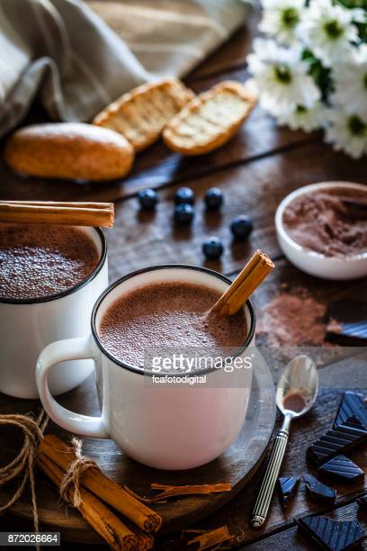 Two homemade hot chocolate mugs on rustic wooden table