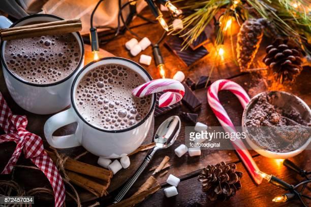 Twee zelfgemaakte warme chocolade mokken met marshmallows op rustieke houten kerst-tafel