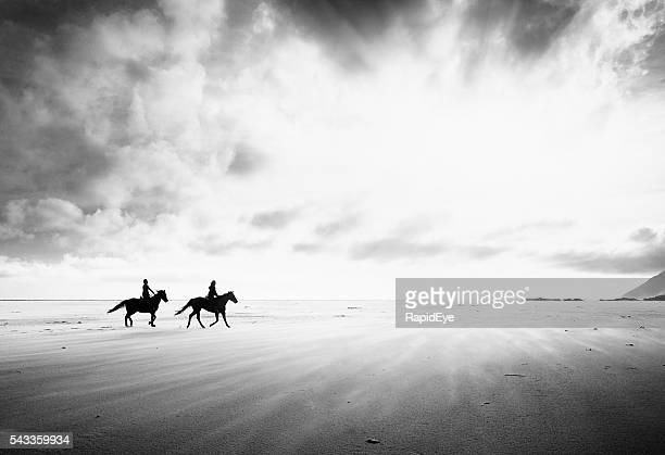 Two horse riders crossing endless stark stretch of sand. Monochrome.