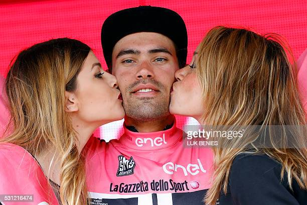 Two hostesses kiss Dutch cyclist Tom Dumoulin of Giant Alpecin team as he bears the leader's pink jersey on the podium in the 7th stage of 99th Giro...