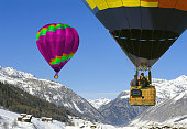 Two hot air balloons flying above winter mountains