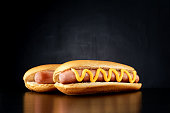 Two hotdogs with big sausage and mustard isolated on black background. Front view.