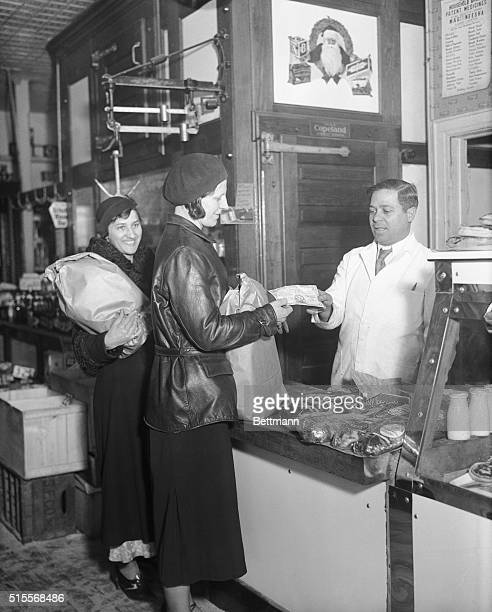 Two housewives of Canarsie Brooklyn are shown purchasing food with the new Canarsie Scrip money at the butcher shop of Anthony Medici as the Greater...