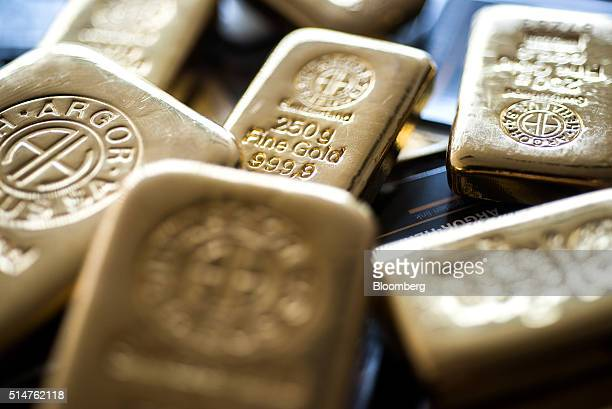 A two hundred and fifty gram gold bar center sits with other gold bars in this arranged photograph at Solar Capital Gold Zrt in Budapest Hungary on...
