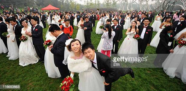 Two hundred newlywed couples pose at the National Stadium better known as Bird's Nest in Beijing on October 10 2010 Thousands of Chinese couples tied...