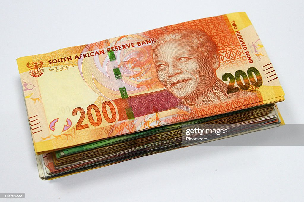 A two hundred rand currency banknote sits on top of a bundle of mixed denomination notes in this arranged photograph at a First National Bank (FNB) branch in Johannesburg, South Africa, on Friday, March 15, 2013. A recovery in mining and manufacturing is giving South Africa's rand and bonds a breather amid concern that growth is slowing while inflation accelerates. Photographer: Nadine Hutton/Bloomberg via Getty Images