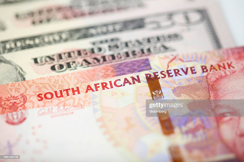 Two hundred South African Rand notes sit on top of American fifty dollar notes in this arranged photograph in London, U.K., on Monday, Aug. 24, 2015. South Africa's rand tumbled the most since 2011 on concern the plunge in commodity prices will deepen as China's economy slows. Photographer: Jason Alden/Bloomberg via Getty Images