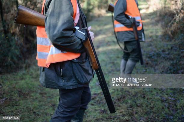 Two hunters hold their loaded shotguns open for safety during a big game hunting on February 14 2015 in La ChapelleGlain western France With 13...