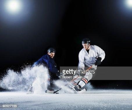 Two ice hockey players challenging for the puck.