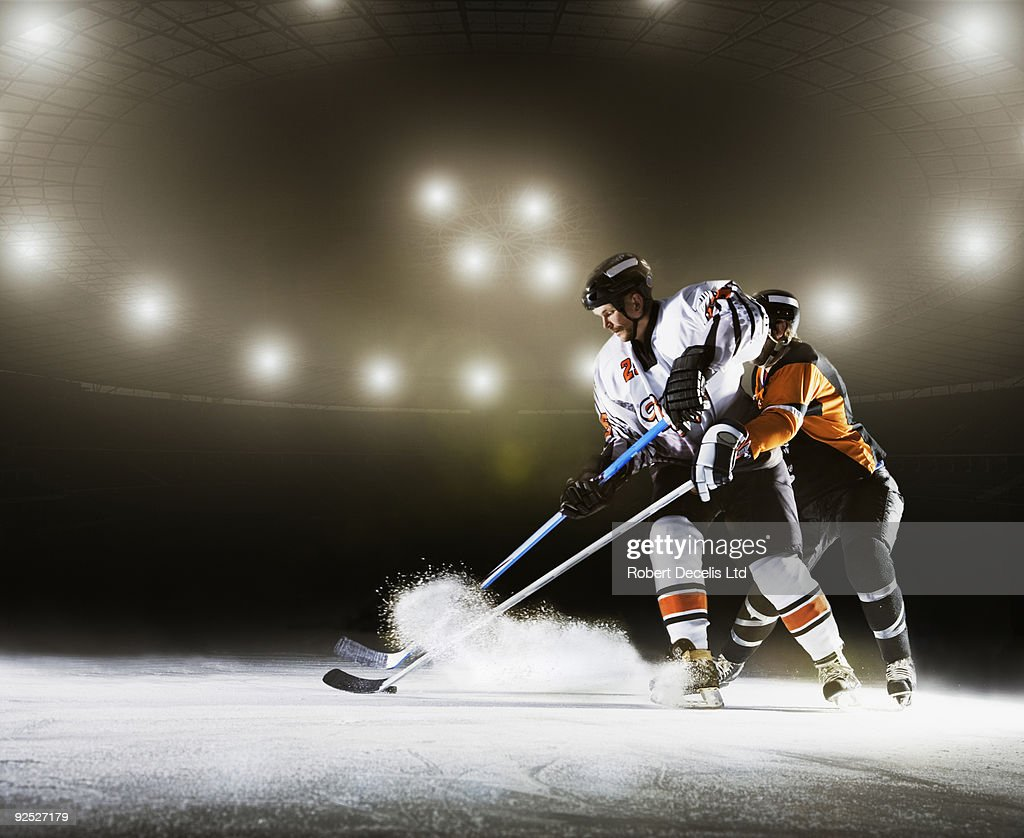 Two ice hockey players competing for puck. : Stock Photo