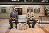 Two identical briefcases in front of two men sitting on bench in subway platform