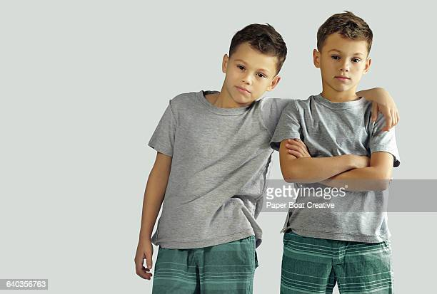 two identical twin brothers standing together