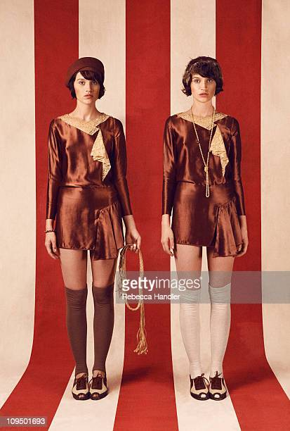 Two identical women wearing 1920s clothing