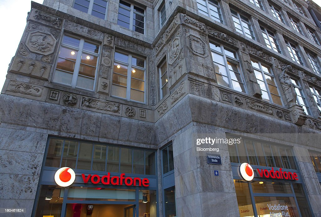 Two illuminated signs for Vodafone are seen on the outside of a store operated by Vodafone Group Plc in Leipzig, Germany, on Thursday, Sept. 12, 2013. Vodafone Group Plc's 7.7 billion-euro ($10.2 billion) bid for Kabel Deutschland Holding AG cleared a major hurdle by winning the backing of at least 75 percent of the German company's shareholders. Photographer: Krisztian Bocsi/Bloomberg via Getty Images
